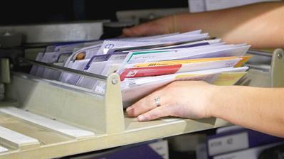 postal-worker-grabs-stack-letters
