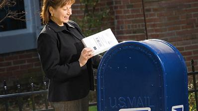 woman-places-package-us-postal-service-mailbox